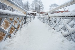 A snow-covered, icy bridge over a waterfall in the Old City in Helsinki, Finland.