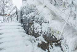 A snow-covered, icy staircase to a bridge over a waterfall in the Old City in Helsinki, Finland.