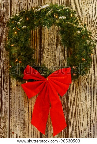 a snow covered lighted christmas wreath with a big red bow on it against a wooden pattern while it is snowing out for your use with room for your text.
