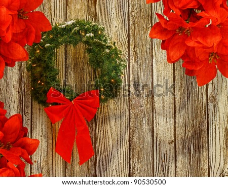 a snow covered lighted christmas wreath with a big red bow on it against a wooden