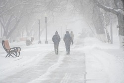 A snow-covered road with people in a storm,blizzard or snowfall in winter in bad weather in the city.Extreme winter weather conditions in the north.People walk through the streets under heavy snowfall