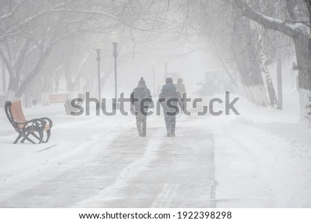 A snow-covered road with people in a storm,blizzard or snowfall in winter in bad weather in the city.Extreme winter weather conditions in the north.People walk through the streets under heavy snowfall Foto stock ©