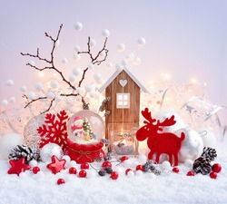 A snow globe with snowman with christmas decorations and toy house on snow and Christmas lights. Festive Christmas background