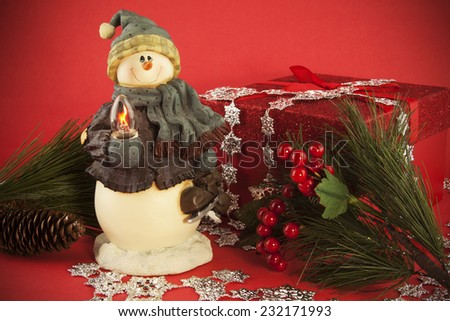 A snow man holiday decoration at the center of a Holiday still life.