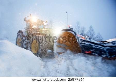 A snow plow clearing a road in winter