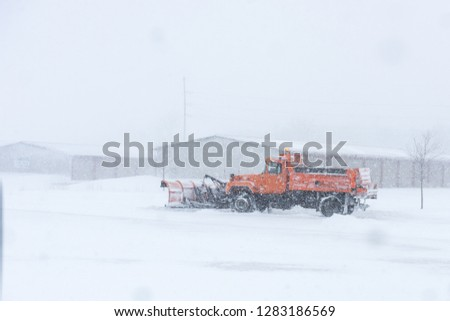 A snow plow removing snow on a street during a blizzard.