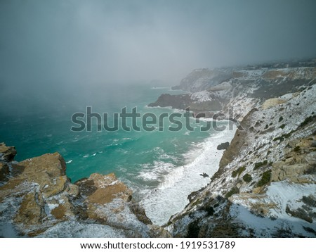 A snow storm covered the seashore. Bright turquoise sea, squally wind, huge waves, bright sun. The concept of bad weather, cold, sudden arrival of winter. Cape Fiolent Sevastopol Crimea top view Foto stock ©