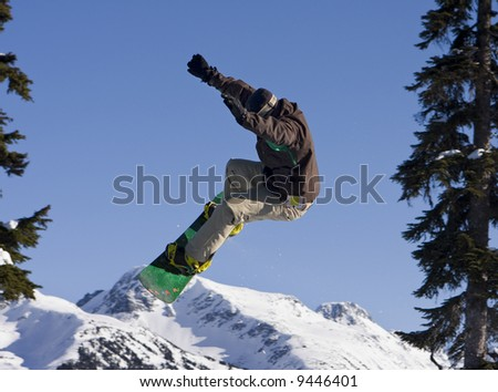 A snowboarder at Whistler catching some big air. With this angle, he appears to be jumping over Blackcomb Mountain.