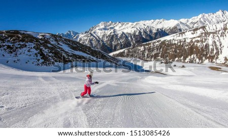 A snowboarder going down the slope in Heiligenblut, Austria. Perfectly groomed slopes. High mountains surrounding the man wearing yellow trousers and blue jacket. Girl wears helm for the protection.