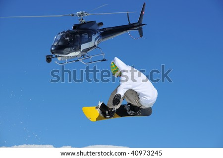 a snowboarder jumping being filmed by a specially adapted helicopter with steady cam