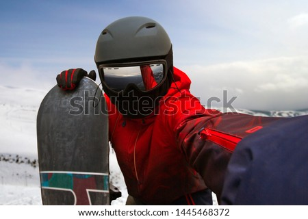 a snowboarder leaning on a board photographs himself on an outstretched hand on a camera #1445468372