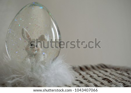 A snowglobe is a container of glass or plastic filled with water, in which there are also small particles (bunny) that stir when shaken and then slowly settle like snow