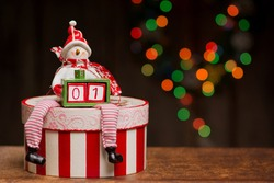 A snowman figure is sitting on a lavishly decorated decoupage box and holding a smaller box with two cubes forming a number one. A beautiful bokeh made with Christmas lights is in the background.