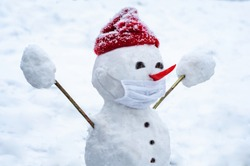 A snowman in a protective mask welcomes Christmas with open arms. New Year 2021. Pandemic coronavirus. Quarantine covid-19. Winter holidays are in jeopardy. Greeting. Children entertainment. Concept