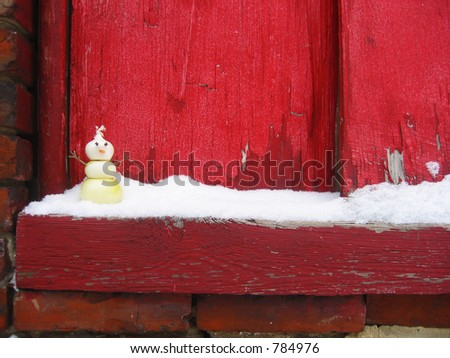 A snowman made of pearl onions, with cloves for eyes and a carrot nose, sits on a snowy windowsill.