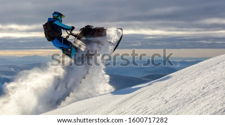 a snowmobile rider jumps in a mountain valley at dawn. sports snow bike with snow splashes and snow trail. bright snowmobile and suit without brands. snowmobilers sports riding. stock photo Stock photo ©