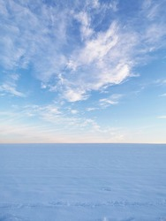 A snowy field in winter - sky and horizon in the afternoon sun