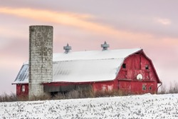 A snowy red barn with silo and basketball hoop is seen with a sunset sky of soft colors.