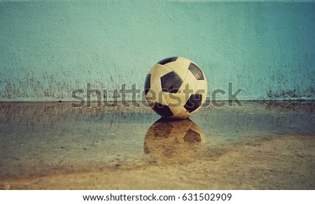 A soccer ball on a cement floor reflected in water.The soccer ball on a cement wall background is a wall. The old soccer ball rests on a cemented floor.Blue wall background