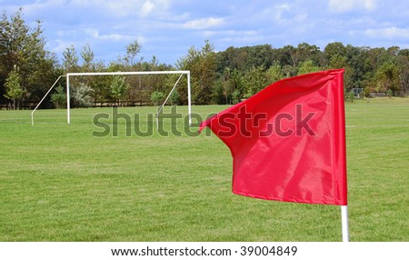 A soccer field with a goal and a red flag