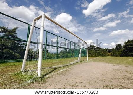 A soccer goal post on a rural soccer field against a blue cloudy sky.