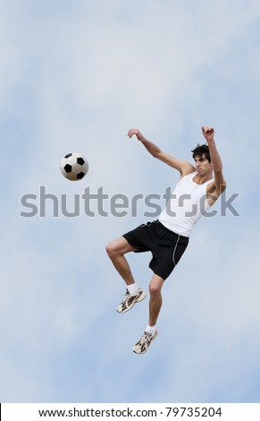 A soccer player jumps up into the air and hits the ball with his knee.