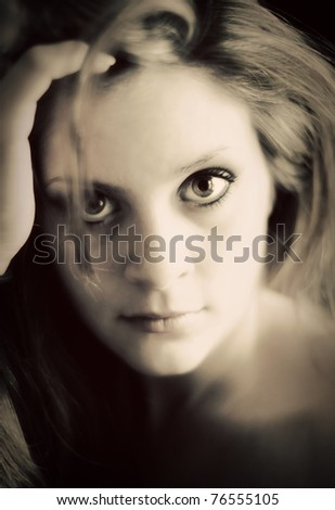 A soft, dreamy, portrait of a young woman gazing directly into camera in a vintage style. Very soft focus, eye is sharp.