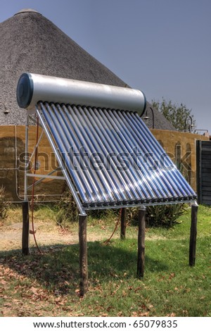 A solar thermal installation, providing hot water to a rural, thatched building behind