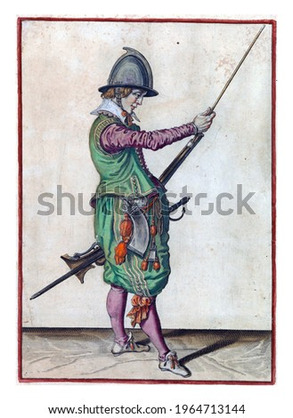 A soldier, full-length, to the right, holding a rudder (a certain type of firearm) by his left thigh with his left hand and sliding the ramrod in the holder under the barrel with his right hand Сток-фото ©