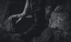 A soldier in military boots overcomes a rift in a brick wall