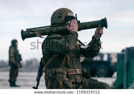 A soldier shoots from a grenade launcher at a military training ground