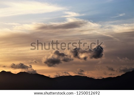 a solemn cloudscape and the  silhouette of a mountain