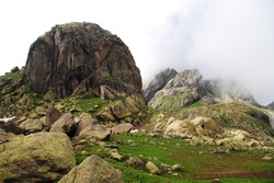 A solemn view of great scale, huge ragged stones, covered with moss, and the thick mist, hanging over the earth.