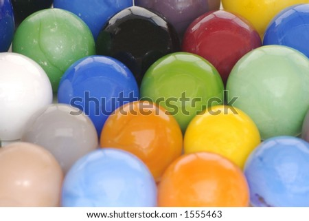 A solid background of brightly colored toy glass marbles.