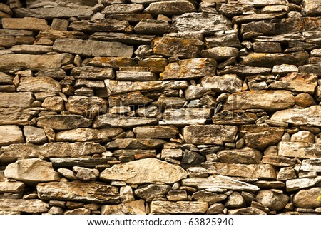 A solid stone wall of an italian alpine house.
