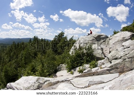 A solitary figure sits atop a stone outcrop atop a mountain in the midst of the Vermont wilderness.