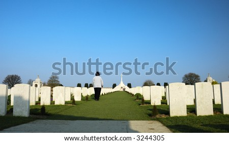 A solitary figure walks up between rows and rows of white headstones in a cemetery filled with graves from the First World War - stock photo