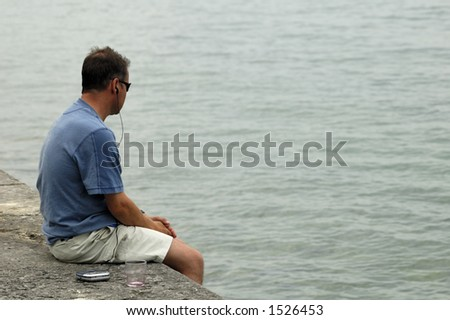 A solitary man, sitting on a sea wall with his hands clasped, gazing into the grey water thoughtfully. A music player and empty wineglass are on the wall beside him.