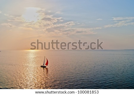 A solitary sailboat in the open sea at the sunset, bird's-eye view