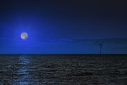 A solitary wind turbine on the sea horizon at night with the water bathed in moonlight. This composite image emphasisies the peaceful constancy  of renewable energy production.