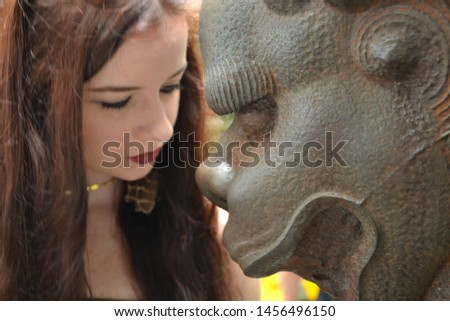 A solumn / glum female western tourist with long brunette hair poses face to face with the face of a chinese statue - asian dragon head or other mythical being