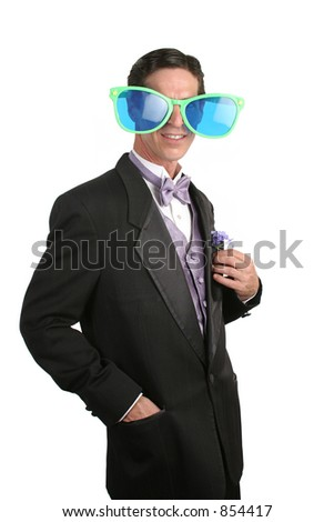 A sophisticated man in a tuxedo with a pair of goofy over-sized sunglasses on. - stock photo