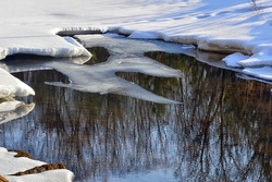 A source of fresh water that does not freeze in winter. Surrounded by snow and ice drifts. Reflection of bushes and beautiful blue sky in the water surface.