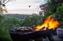 A South African barbecue braai with meat on the fire in front of a lush valley landscape and a beautiful orange sunset.