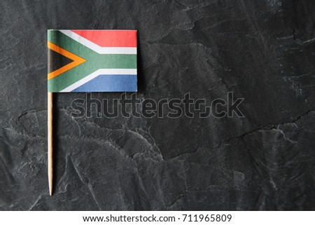 A South African flag toothpick on a black slate background. Heritage day concept image.