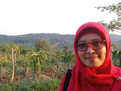 A Southeast Asian woman with red glasses look at camera in front of a field. Muslim girl in a farmland area in Subang, West Java, Indonesia. Behind are some trees : dragon fruit, pineapple, and papaya