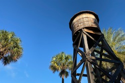 a southern farm wooden water tower with palm trees