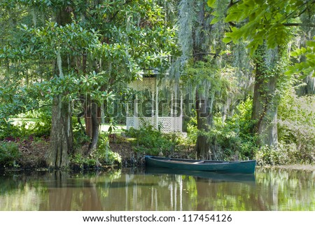 A southern scene with gazebo, pond, canoe, and cypress trees.
