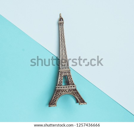 A souvenir statuette of the Eiffel Tower on a white blue pastel background. Top view. Minimalist trend.