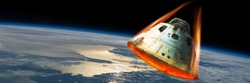 A space capsule reenters the earths atmosphere causing the heat shield to glow from the friction of tremendous speed. Elements of this image courtesy of NASA.